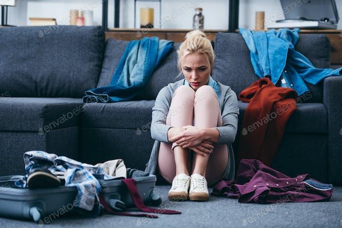 traurige Frau sitzt mit vereinzelter Kleidung und Koffer, nachdem sie sich mit einem Freund getrennt hat