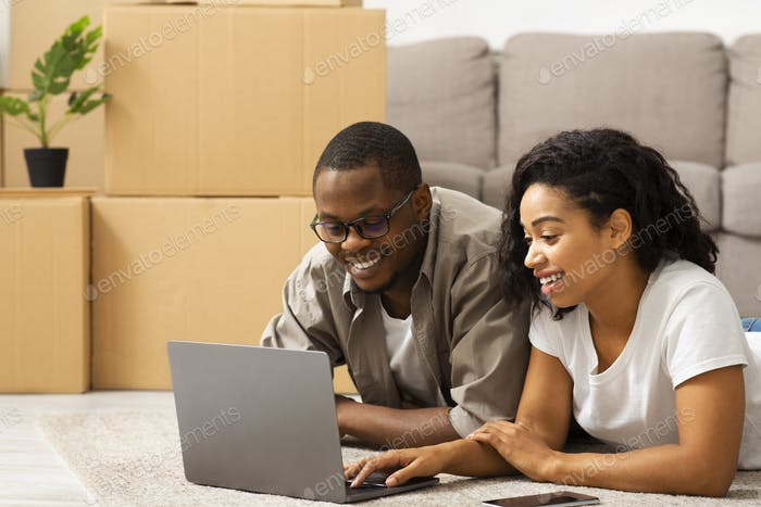 Couple deciding how to design their home with laptop