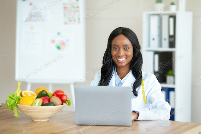 Joyful black female dietitian with laptop consulting patient online at clinic, empty space