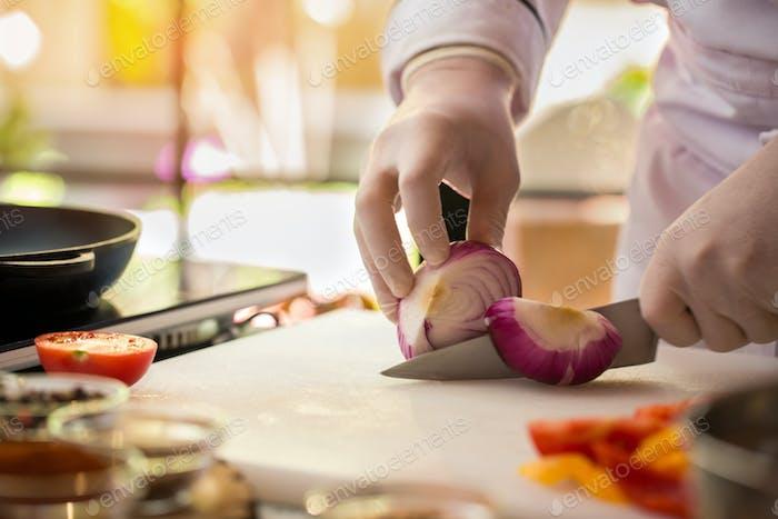 Knife cuts purple onion