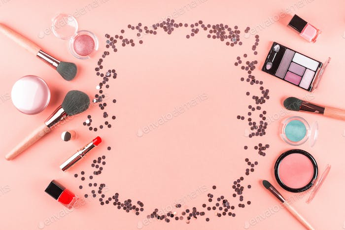 Make up products on pink coral with confetti frame