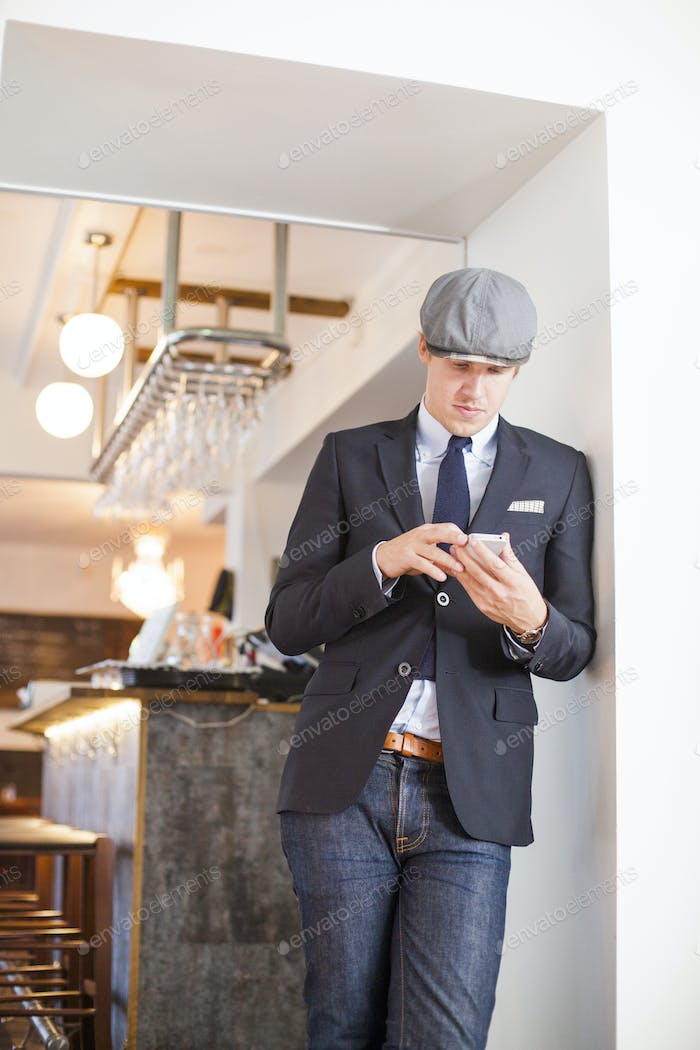 Man using smart phone while standing against bar counter in restaurant