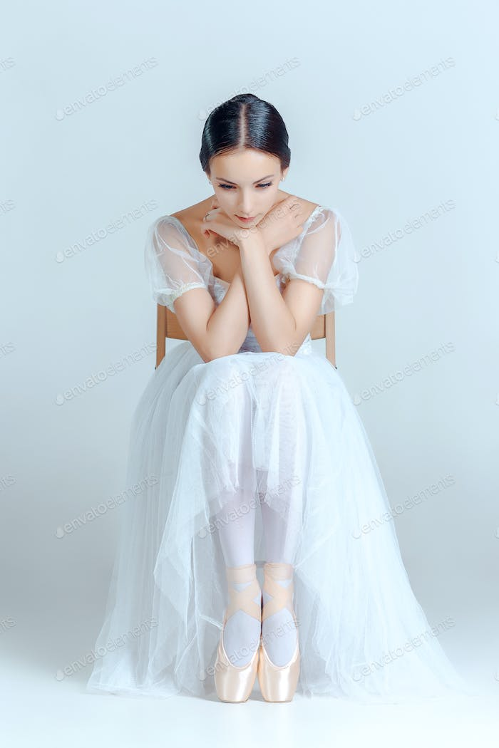 Professional ballerina sitting with her ballet shoes on the gray background