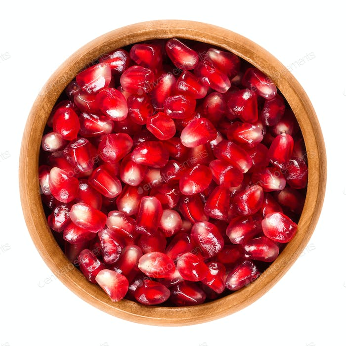 Fresh pomegranate seeds in wooden bowl over white