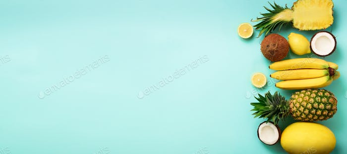 Fresh organic yellow fruits over blue background. Monochrome concept with banana, coconut, pineapple