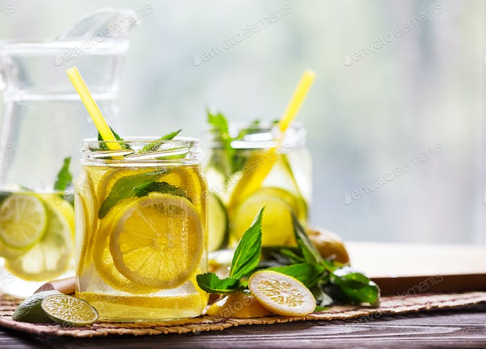 Banks and a jug with cold lemonade and ingredients on a wooden t