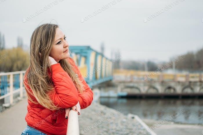 Umarmen Sie sich als Single, Kunst des Seins glücklich Single. Frau in roter Jacke geht allein am Fluss