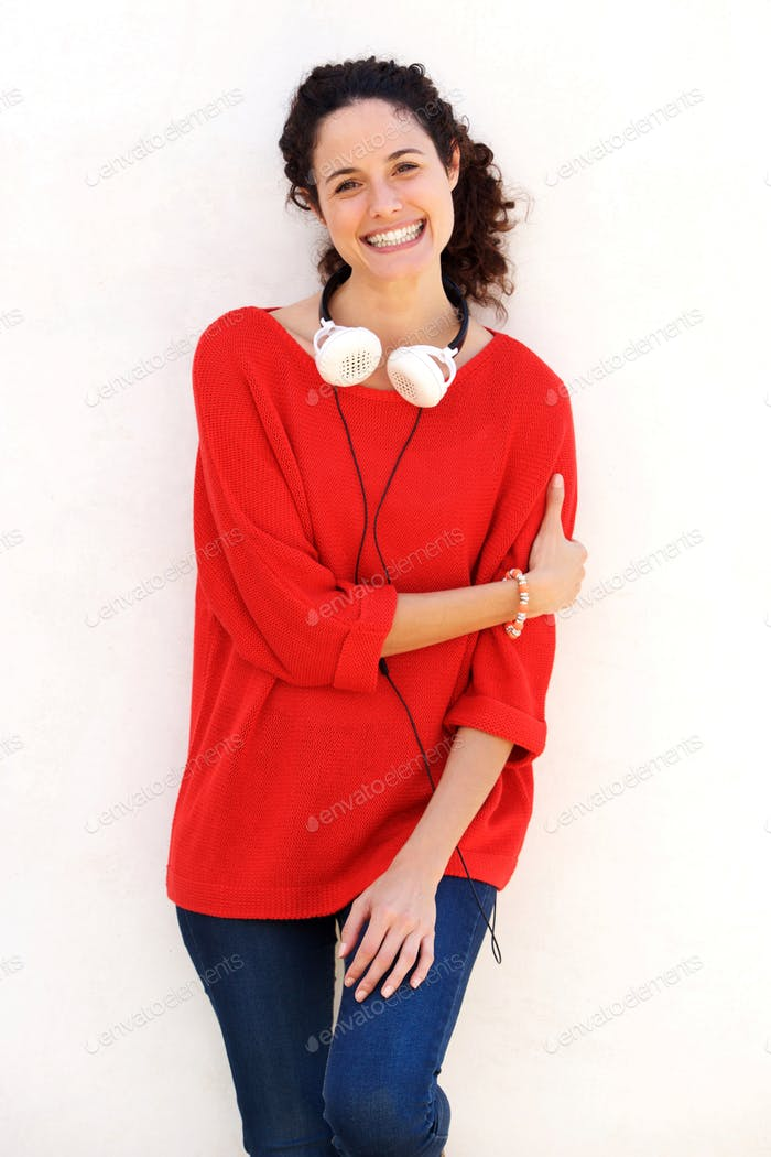 happy young woman standing against white wall with headphones