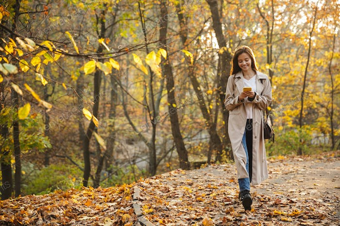 Image of young woman using smartphone while walking in autumn park