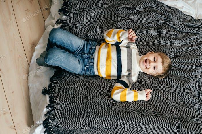 Happy little boy having fun on bed