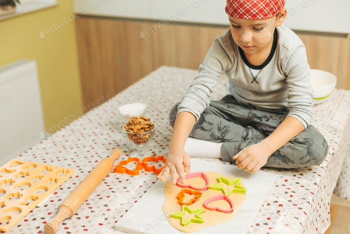 Boy making biscuits using Christmas cookie molds