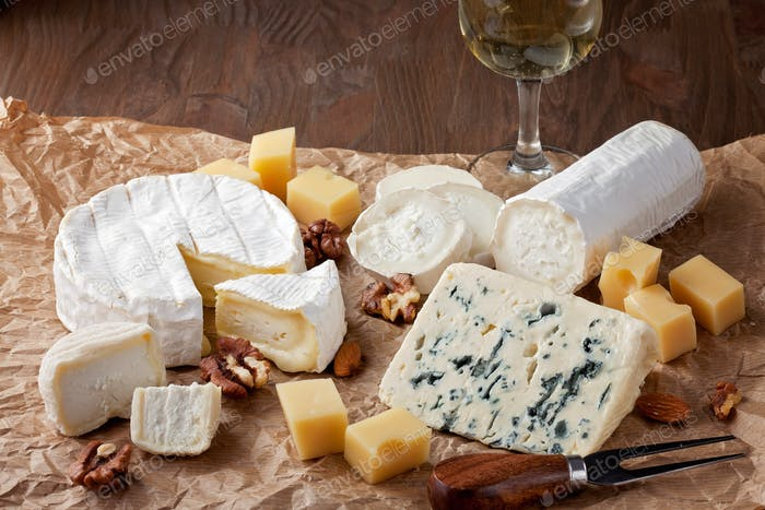 Variety of different cheese with wine. Camembert, goat cheese, roquefort, gorgonzolla, gauda