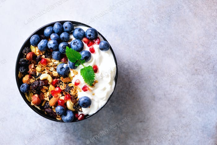 Tasty homemade granola, yogurt, fresh organic berries, pomegranate, mint on grey concrete background