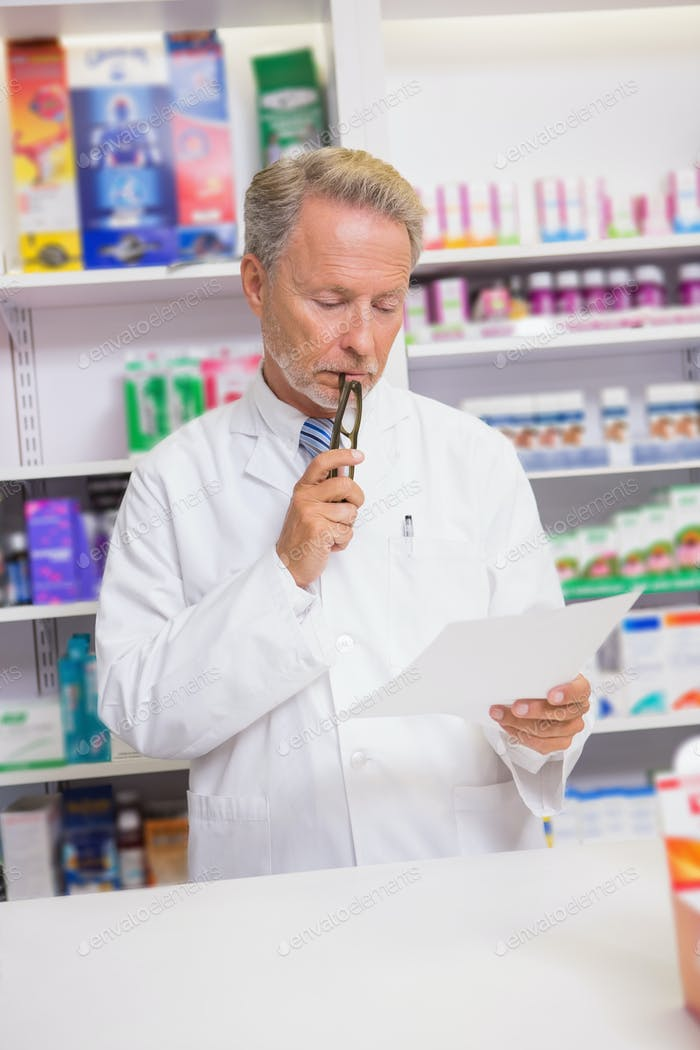 Serious senior pharmacist reading prescription in the pharmacy