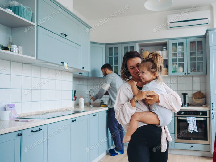 dad, mom, little daughter in the kitchen