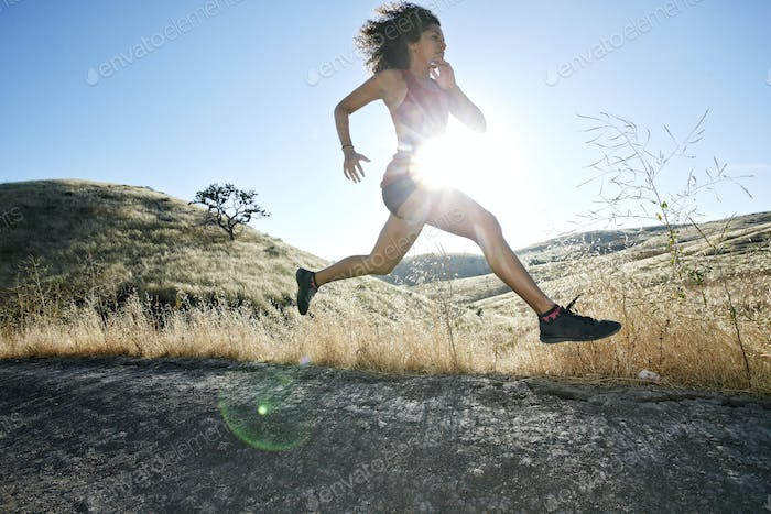 Young woman with curly brown hair running in urban park.