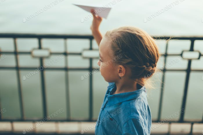 Girl playing with toy paper airplane