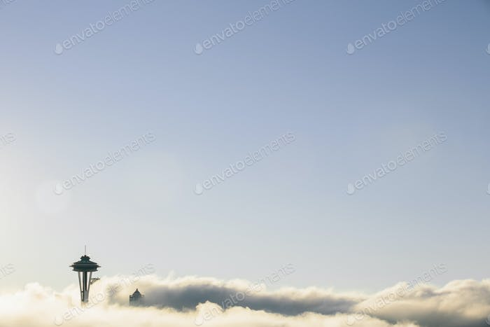 The top of the Space Needle tower seen rising above a thick layer of cloud and blue sky.