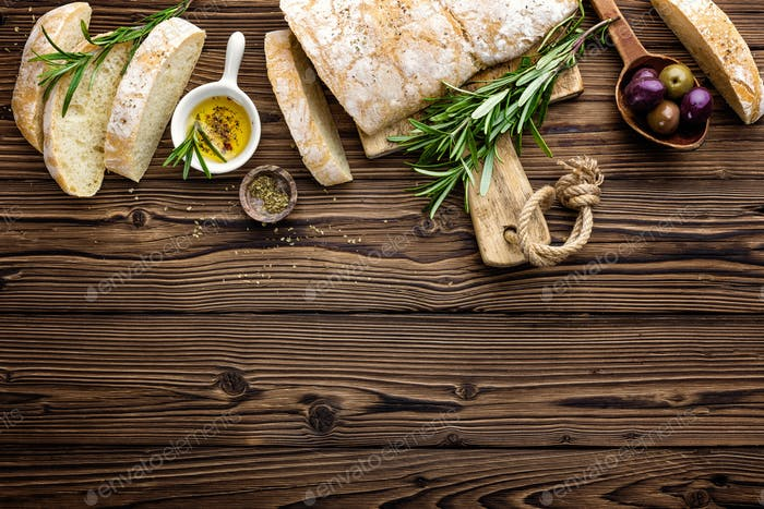 Delicious homemade italian ciabatta bread with olive oil and olives on wooden rustic background