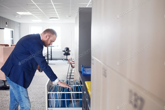 Mid adult man looking through files in cabinet