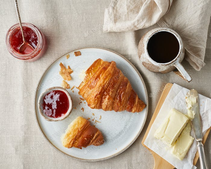 One delicious croissants on plate and hot drink in mug. Morning French breakfast
