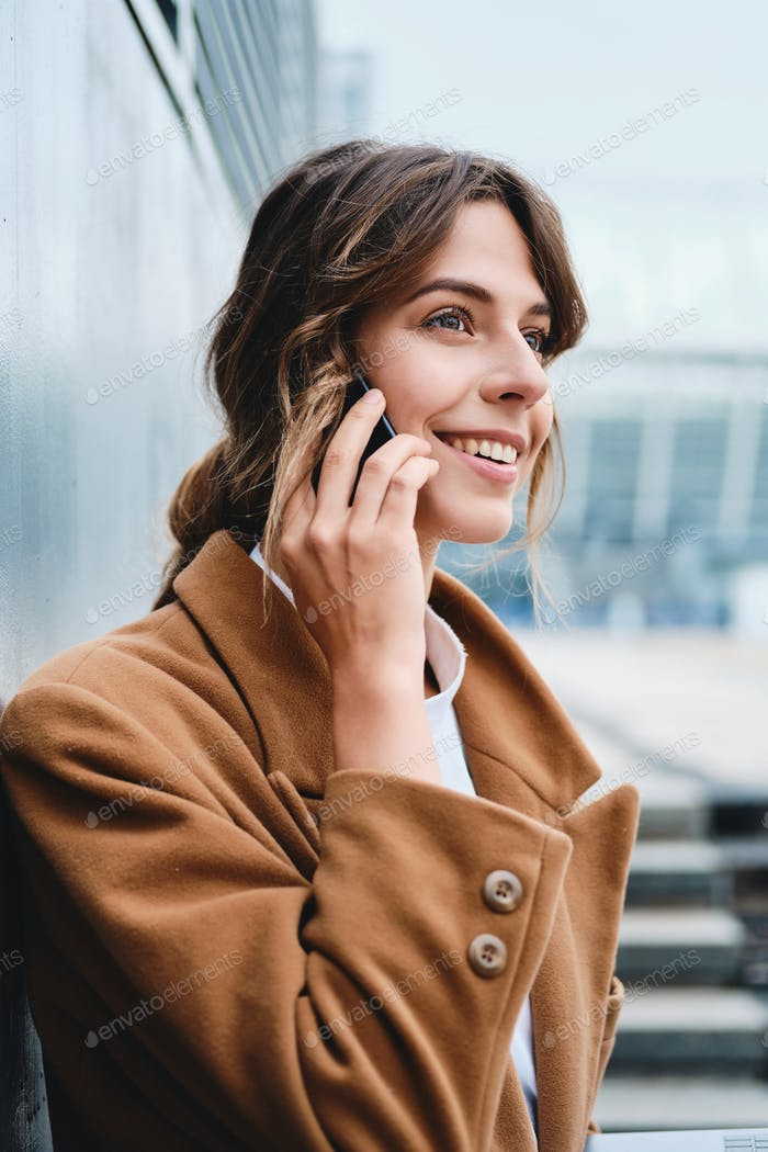 Young pretty stylish businesswoman in coat happily talking on cellphone on city street