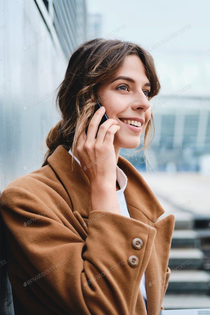 Junge ziemlich stilvolle Geschäftsfrau im Mantel glücklich reden auf Handy auf Stadtstraße