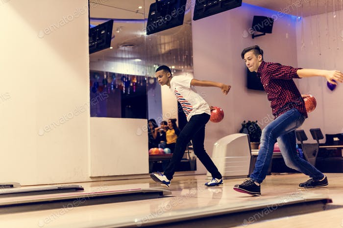 Teen boys bowling together