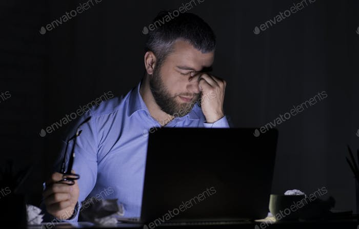 Tired businessman working with laptop in darkness, touching his eyes