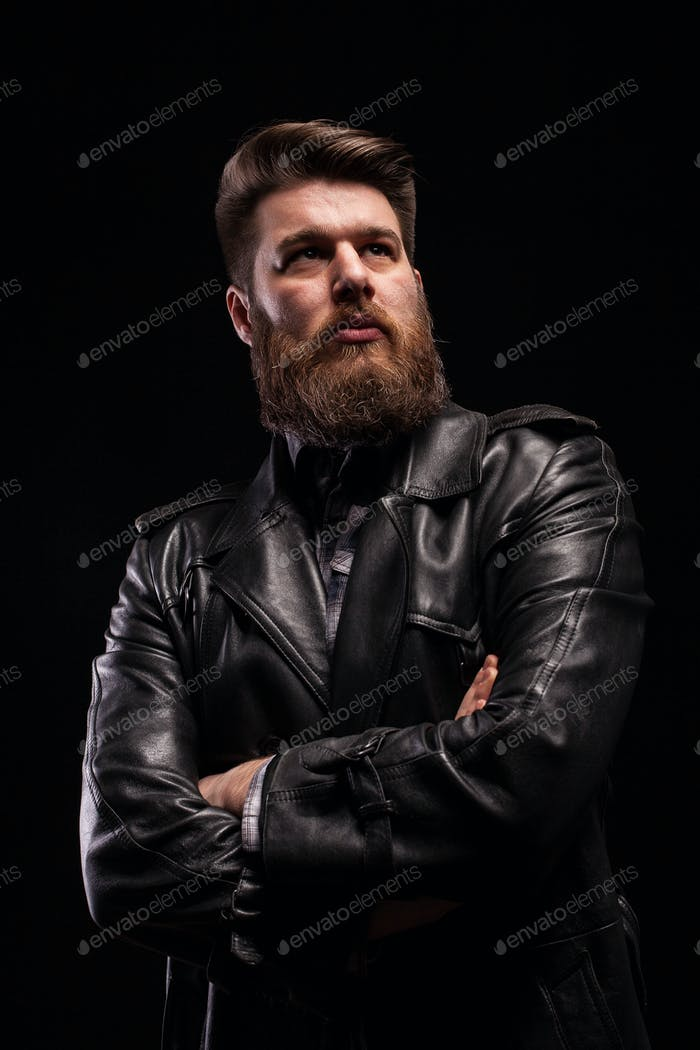 Portrait of Handsome bearded man wearing a leather jacket with serious expresion over black