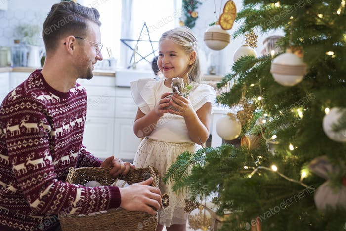 Father and daughter decorating the Christmas tree