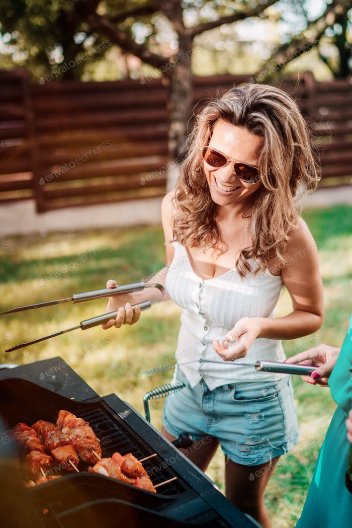 woman smiling and cooking at barbecue grill party. Friends, people lifestyle concept
