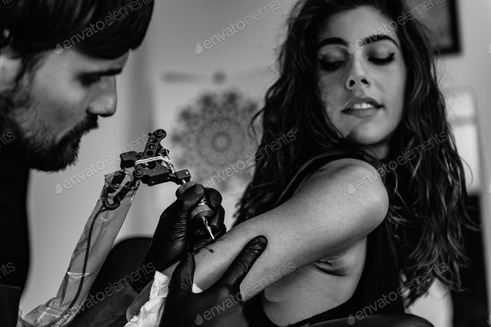 Tattoo artist tattooing young woman