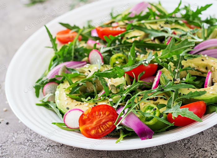 Healthy salad of fresh vegetables - tomatoes, avocado, arugula, radish and seeds
