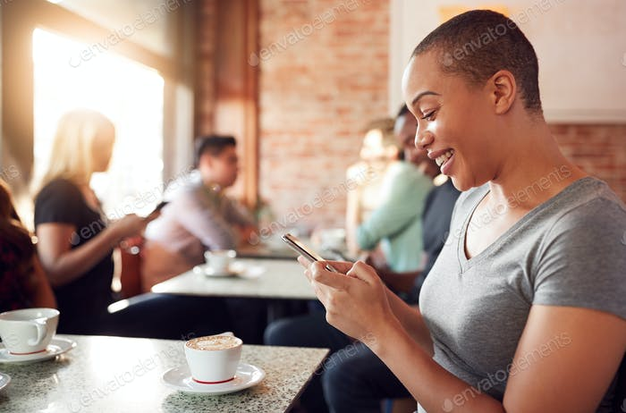 Frau mit Handy sitzen am Tisch in Coffee Shop
