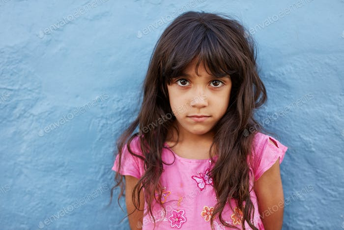 Innocent little girl standing against blue wall