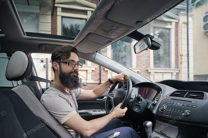 Glücklicher charismatischer Mann Autofahren