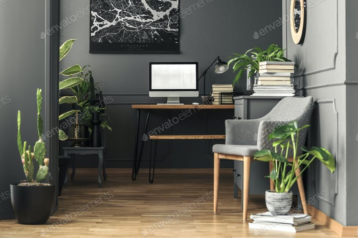 Plant next to grey armchair in home office interior with mockup