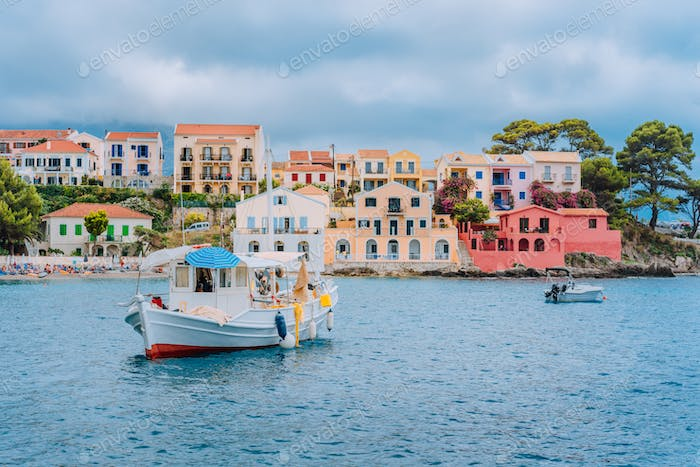 Fishing boat at anchor in blue sea bay of Assos village. Vivid colored houses with clouds in