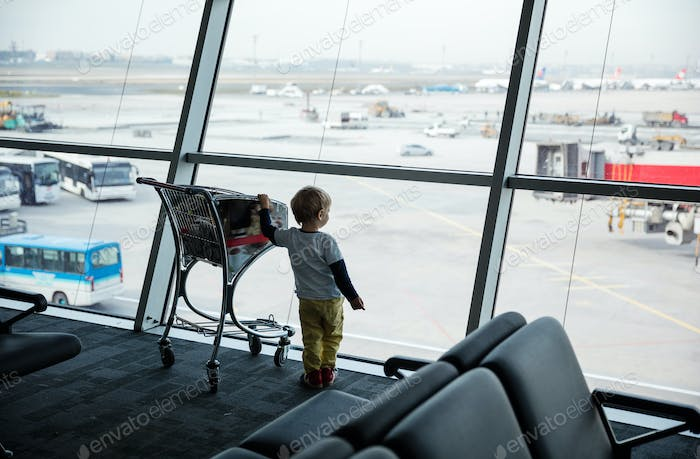 Little boy standing at window in airport and looking at landing field