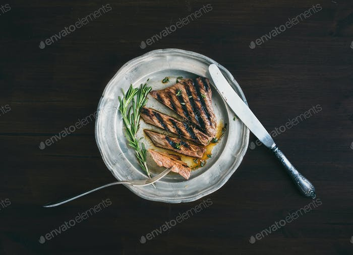 Beef steak cut into pieces with rosemary, knife and fork on a vi