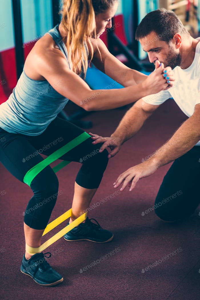 Woman exercising with personal trainer in a gym