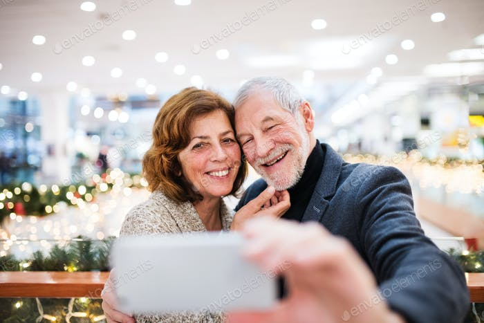Senior couple with smartphone doing Christmas shopping.