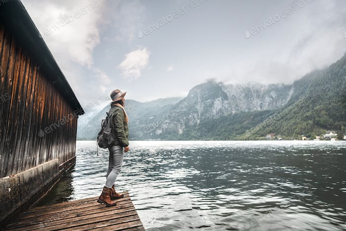 Young girl with a backpack by the lake