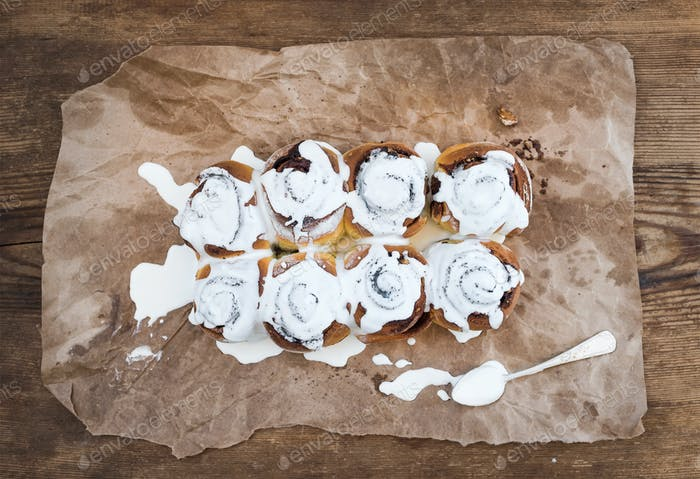 Cinnamon Rolls With Cream Cheese Icing On Piece Of Oily Craft Paper