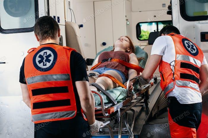 Weibliches junges Opfer des Unfalls liegt auf einer Trage in einem Krankenwagen