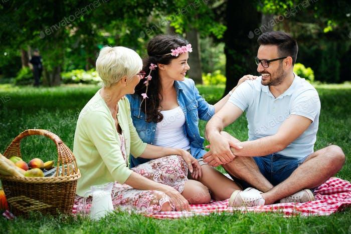Young woman and man with grandmother smilling in a park on a sunny day