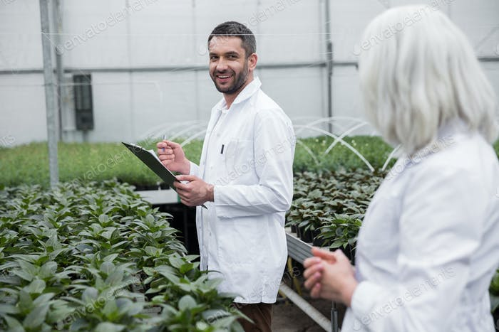 Smiling young man and mature woman standing in greenhouse