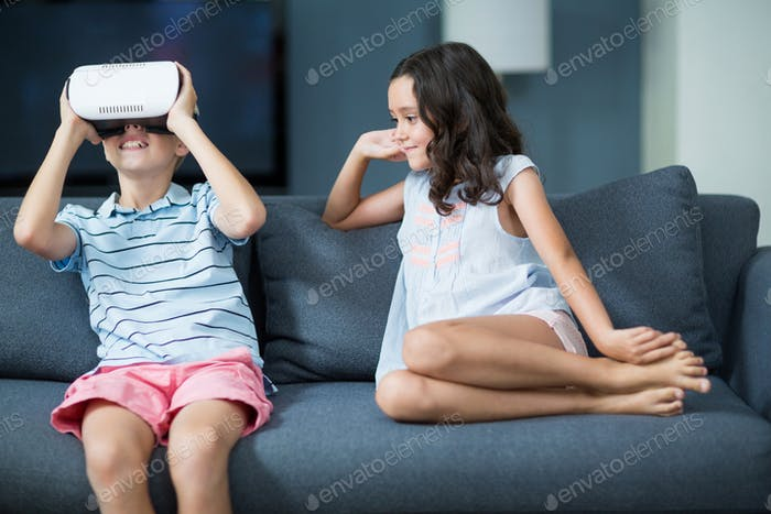 Girl looking at her brother using virtual reality headset in living room