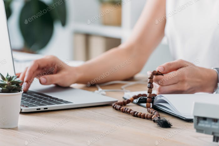 cropped view of businesswoman using laptop and holding rosary beads at workplace